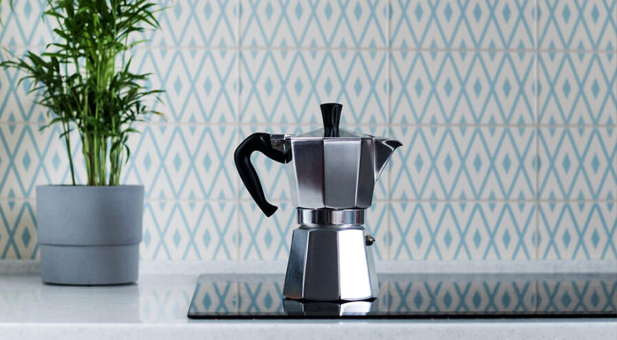 Italian Moka pot on black stovetop with plant in background