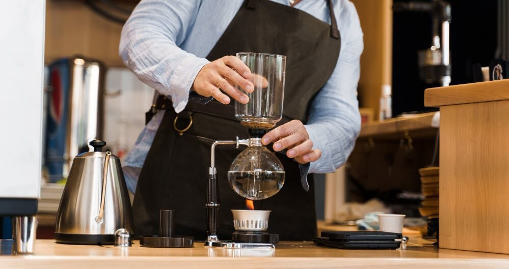 man making coffee by siphon