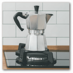moka pot in stovetop on wooden table