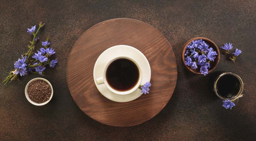 Chicory flowers and coffee cup on dark brown wood table