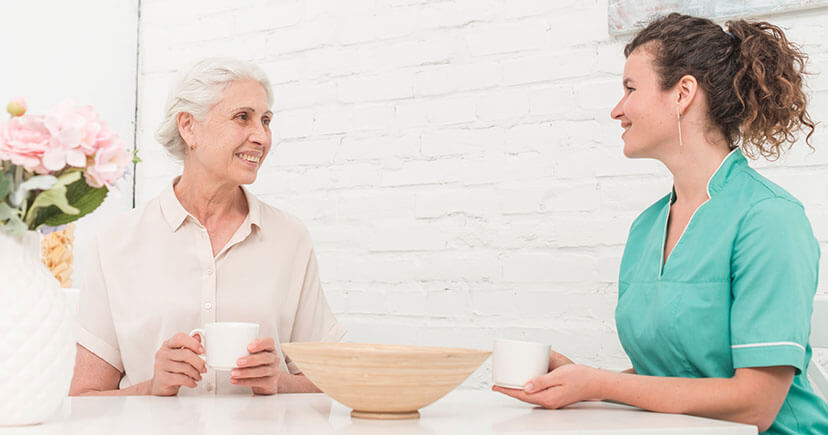 Old patient and nurse drinking Coffee with white background