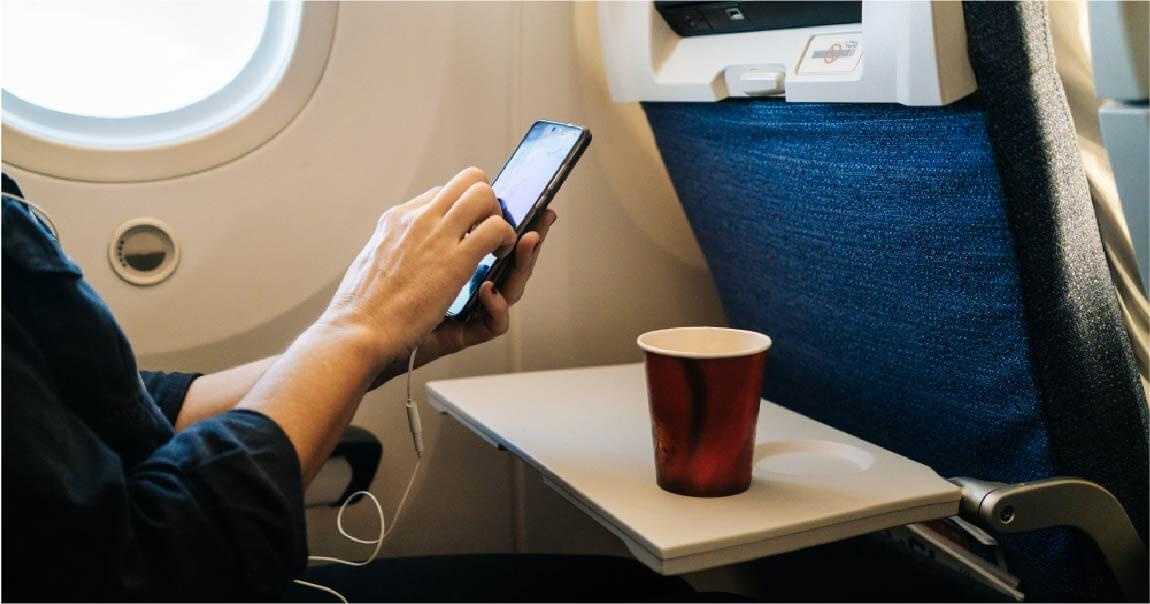 A hand using mobile and drinking red coffee in plane