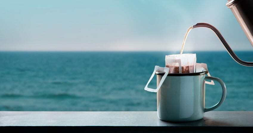 brewing drip coffee using drip bag on sea site