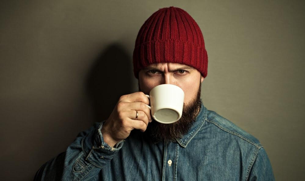 A beard man drinking coffee