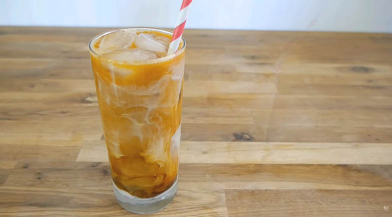 Thai iced coffee in glass on wood table