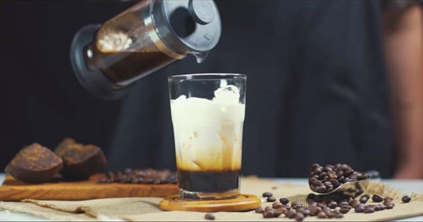 A man making Es Copi Susu Coffee in glass