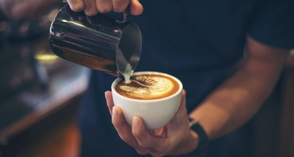 man making latte in coffee shop