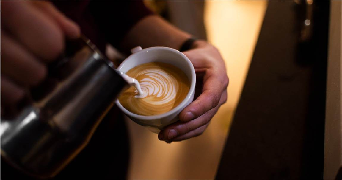 A man Making flat white coffee in cup