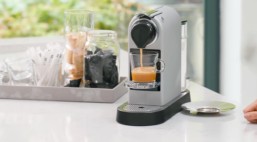 coffee brewing in Nespresso on white table
