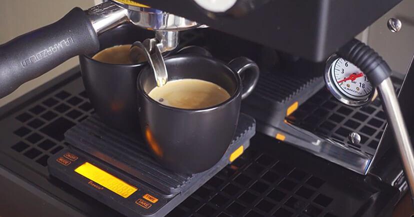 Espresso-Crema droping in black cup from machine