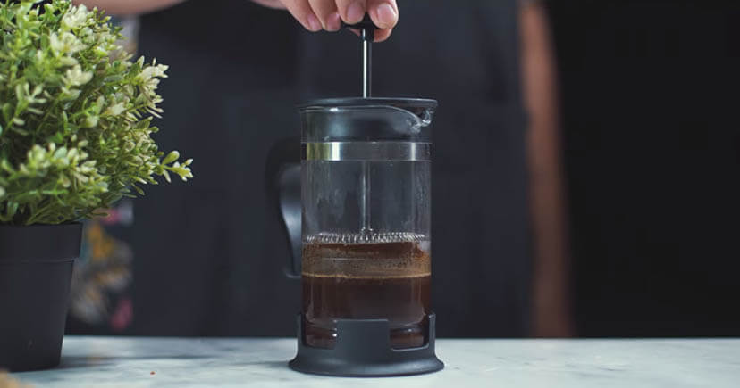 A man hand brewing coffee on table near plant