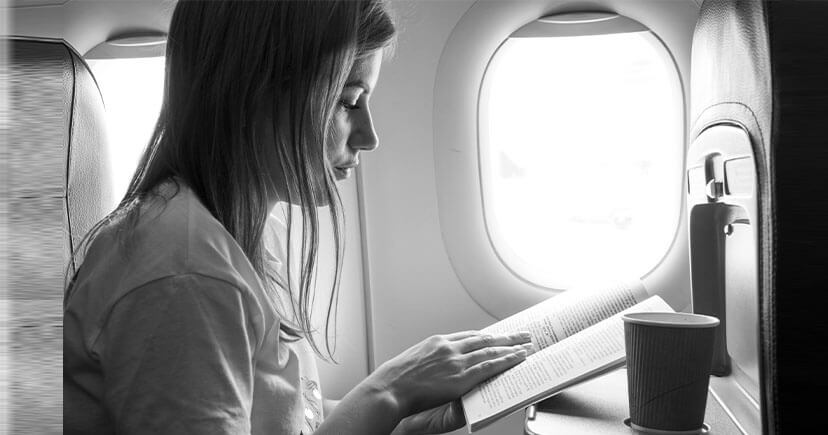 A girl reading book and drink coffee in plane