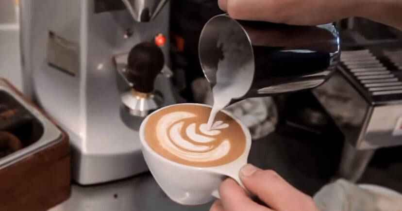 A man making Mocha coffee in white cup