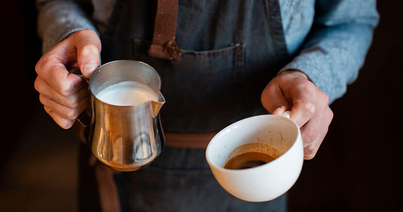 Man hands holding milk and cup of coffee