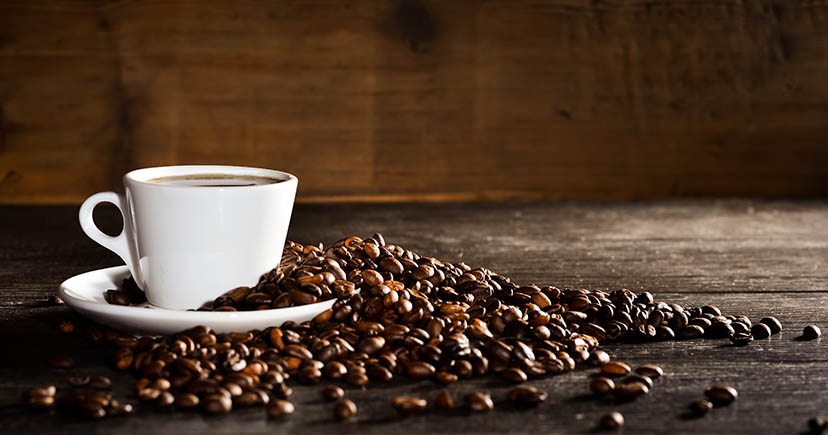 A white coffee cup and coffee beans on wood table