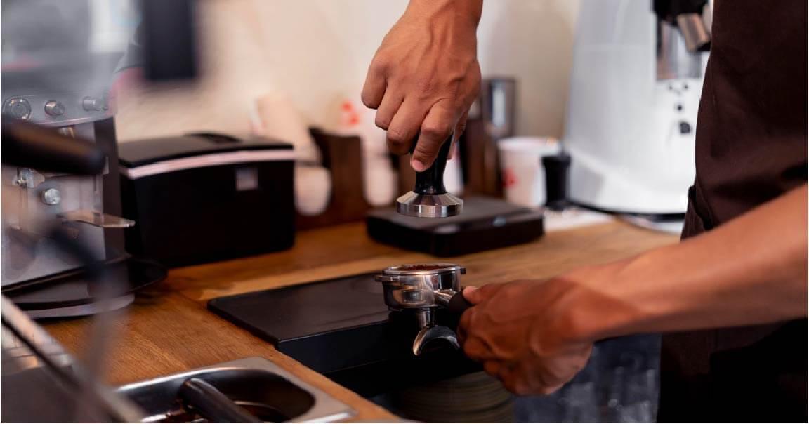 man making galao coffee in kitchen